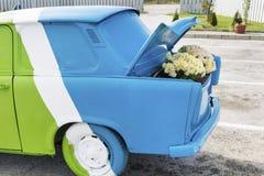 Blumen unter der Haube eines alten Autos Stockbilder