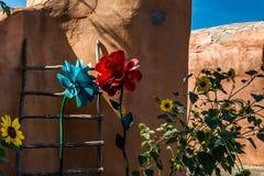 Blumen unter einer Lehmziegelmauer Stockbilder