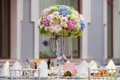 Blumen, Weingläser, Servietten und Salat auf dem Tisch Stockfotos