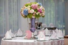 Blumen, Weingläser, Servietten und Salat auf dem Tisch Lizenzfreies Stockbild