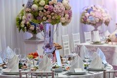 Blumen, Weingläser, Servietten und Salat auf dem Tisch Stockfotografie