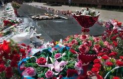 Blumen zum ewigen Feuer am Denkmal Lizenzfreies Stockfoto
