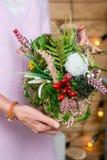 Blumenanordnung in den Händen des Floristen in dem Stadium der Fertigstellung lizenzfreie stockfotos