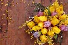 Blumenanordnung für Tulpen, Mimosen und Weiden auf einem Holztisch Lizenzfreies Stockfoto