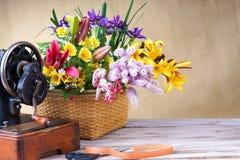 Blumenanordnung mit alter Nähenmaschine Stockfotografie