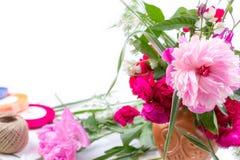 Blumenanordnung mit einem schönen Blumenstrauß von rosa Pfingstrosenblumen, von Kornblumen und von roten Rosen auf einem weißen H Stockfotos