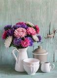 Blumenastern in einem Weiß emaillierten Pitcher und Weinlesetonware - keramische Schüssel und emailliertes Glas, auf einem blauen Lizenzfreies Stockbild