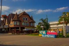 BLUMENAU, БРАЗИЛИЯ - 10-ОЕ МАЯ 2016: знак colorfull blumenau расположенный перед старым немецким домом стиля в центре города Стоковые Фото