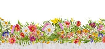 Blumenbeet mit den Dahlienblumen und weißer hölzerner Terrasse, lokalisiert Stockfotos