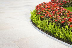 Blumenbeet mit krummlinigen Formen mit klarem Steinboden Stockbild