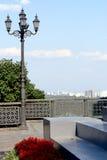 Blumenbeet von roten Blumen Nahe dem Laternenpfahl und im Abstand können Sie das Schattenbild der Stadt sehen Stockbilder
