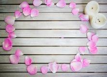 Blumenblätter von rosa Rosen auf einem weißen Holztisch stockfotos