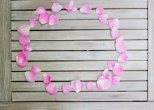 Blumenblätter von rosa Rosen auf einem weißen Holztisch lizenzfreies stockfoto