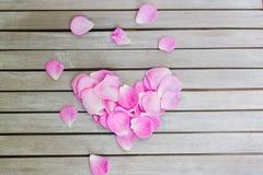 Blumenblätter von rosa Rosen in einem Herzen formen auf einen weißen Holztisch stockfoto