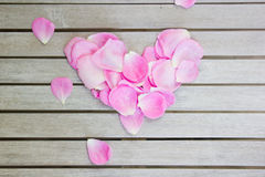 Blumenblätter von rosa Rosen in einem Herzen formen auf einen weißen Holztisch stockbild