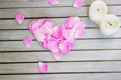 Blumenblätter von rosa Rosen in einer Herzform und in einer Kerze auf einem weißen wo lizenzfreie stockfotografie