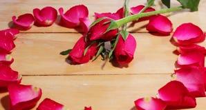 Blumenblätter von Rosen auf dem Tisch Lizenzfreie Stockfotos