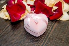 Blumenblatt stieg mit Geschenkbox auf Tabelle valentine Lizenzfreie Stockbilder