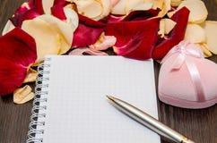 Blumenblatt stieg mit Geschenkbox und leerer Karte auf Tabelle Rote Rose und Inneres über Weiß Lizenzfreie Stockfotos
