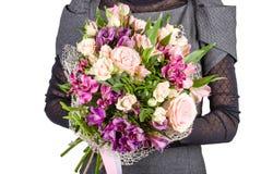Blumenblumenstrauß in den Händen des Mädchens lizenzfreies stockbild