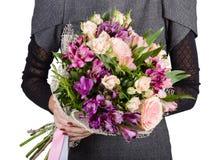 Blumenblumenstrauß in den Händen des Mädchens stockfotografie