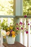 Blumenblumenstrauß im Eimereimer auf Eingangsterrasse Einfach, Landhausstilsommerausgangsdekor lizenzfreie stockbilder