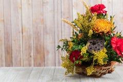 Blumenblumenstrauß im Korb auf hölzerner Tabelle Stockfotografie
