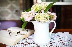 Blumenblumenstrauß innen mit Buch und Gläsern Lizenzfreies Stockfoto