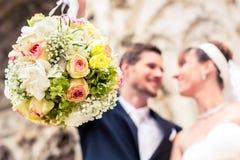 Blumenblumenstrauß vor Jungvermähltenpaaren lizenzfreie stockfotos