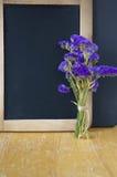 Blumenblumenstrauß gesetzt neben Tafel Lizenzfreie Stockbilder