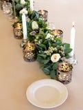 Blumendekoration der eleganten Hochzeit mit weißen brennenden Kerzen, Rosen und Eukalyptus stockfoto