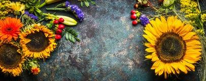 Blumendekoration mit Sonnenblumen und Fallblumen und -blätter auf dunklem Weinlesehintergrund, Draufsicht Stockfotografie