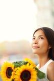 Blumenfrau, die das Sonnenblumenlächeln glücklich hält Stockfotos