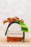Blumengesteck mit Calla-Lilien, Blütenschweif und dem Grün an Stockbild