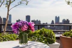 Blumengesteck mit Rosen, Hortensie, Orchideen mit Stadthintergrund Stockbilder