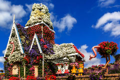 Blumenhaus, Puppen und Strauß auf dem Hintergrund von Wolken lizenzfreies stockbild