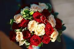 Blumenhochzeitsblumenstrauß von weißen und roten Rosen mit goldenen Brautbändern lizenzfreie stockfotografie