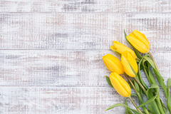 Blumenkarte mit gelben Tulpen über hölzernem Hintergrund der Weinlese Stockfotografie