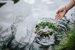 Blumenkranz in der Hand der Frau lizenzfreie stockfotos