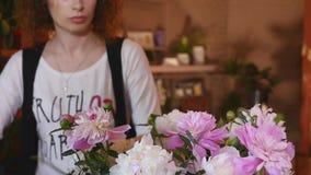 Blumenladen, Florist Arranging Modern Bouquet, junge hübsche Floristen arbeiten am Blumenshop, der Blumenstrauß macht stock footage
