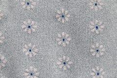 Blumenmuster auf einem grauen Gewebe Stockfotos