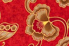 Blumenmuster auf rotem Batik Stockbild