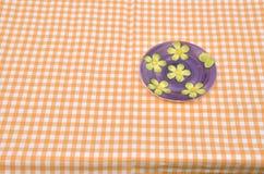 Blumenplatte auf gelber Tischdecke Stockbild