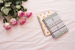 Blumenrahmen mit erstaunlichen rosa Rosen und Notizbüchern auf rosa Bettlaken im Schlafzimmer Freiberuflich tätiger Arbeitsplatz  lizenzfreies stockfoto