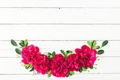 Blumenrahmen mit roten Pfingstrosen und Blättern auf weißem hölzernem Hintergrund Flache Lage, Draufsicht Muster gemacht von den  Lizenzfreies Stockbild