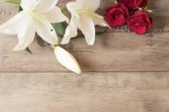 Blumenrahmen mit weißen Lilien der Betäubung und roten Rosen auf hölzernem Hintergrund Kopieren Sie Platz Hochzeit, Gutschein, va Lizenzfreie Stockfotos