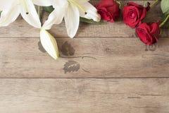 Blumenrahmen mit weißen Lilien der Betäubung und roten Rosen auf hölzernem Hintergrund Kopieren Sie Platz Hochzeit, Gutschein, va Lizenzfreies Stockfoto