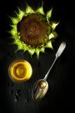 Blumensonnenblume und -Färberdistelöl in einem Löffel Lizenzfreie Stockfotografie