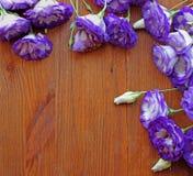 Blumensträuße des purpurroten Eustoma blüht auf dem Holztisch Lizenzfreie Stockfotografie