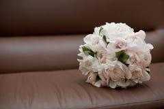 Blumenstrauß auf braunem ledernem Stuhl Stockbild